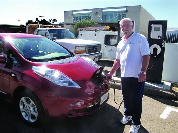 """Jim Ruby, facilities management fleet director for the University of California, San Diego, charges one of the school's five Nissan LEAFs, acquired as part of the University's """"Tailpipe Endgame"""" sustainability initiative."""