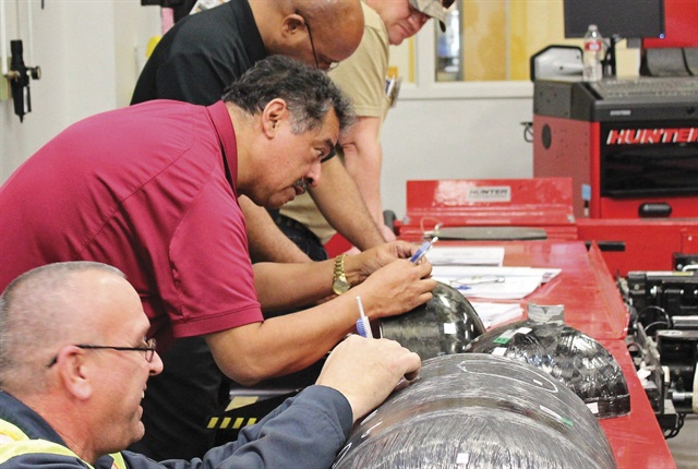 During hands-on practical skill building, technicians use a depth gauge to assess damage on a compressed natural gas (CNG) cylinder.