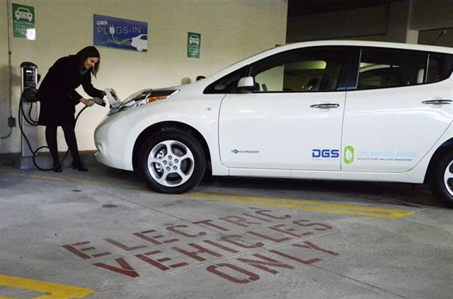 DGS Employee Rebecca Kirk plugs in a new state electric vehicle at a public state garage in downtown Sacramento. Photo courtesy of California DGS.