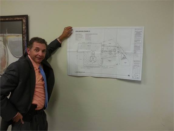 Sal Milazzo holds up the floor plans for the new 25,000 sq.-ft facility where Windy City Limousine will build its new fleet headquarters and refueling station.Photo courtesy Windy City Limousine