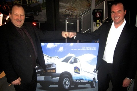 Glenn Weir of Best Western (left) and Kent Rathwell of Sun Country Highway unveil an artist's rendering of the VIA Motors electrified shuttle van.