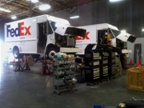 Pictured are two conventional FedEx Express vehicles being retrofit